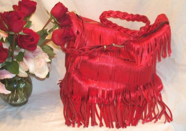 Metallic lipstick red fringed leather purse. That's a whole lot of look. By DBag. Wait, that's not right. By DLeather
