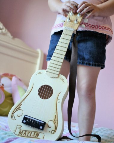 I would absolutely love to give this beautiful handmade personalized guitar to some special little someone. We'll see who turns out to be musical! By ScissorMill