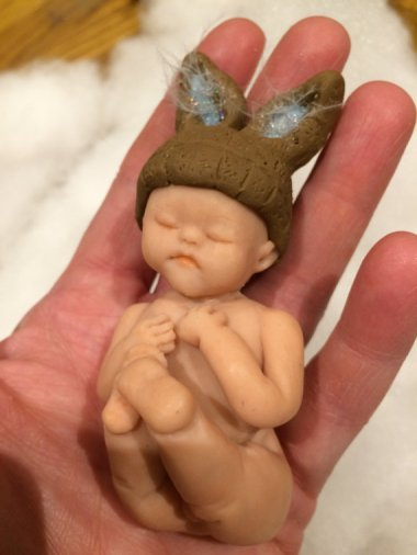 This is intended as a baby shower gift. My daughter once shat herself so hard, it shot up the back of her diaper and hit her in the head. The cleanup is a blur, but I'm pretty sure I didn't stop to form bunny ears with it first. By FimoAlive